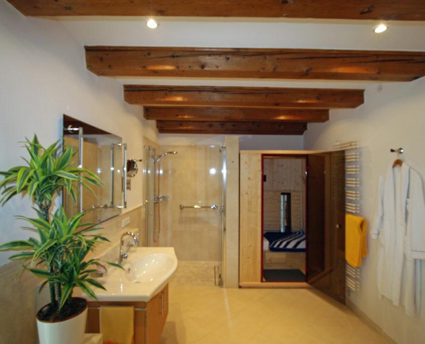 Holzbalken und elegante Lichttechnik geben den Bad einen besonderen Flair