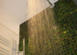 Grüne Glasmosaikfliesen in der Regendusche nach Badsanierung