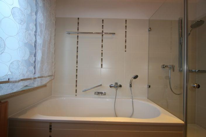 Badewanne und Dusche im kleinen Bad mit Fenster